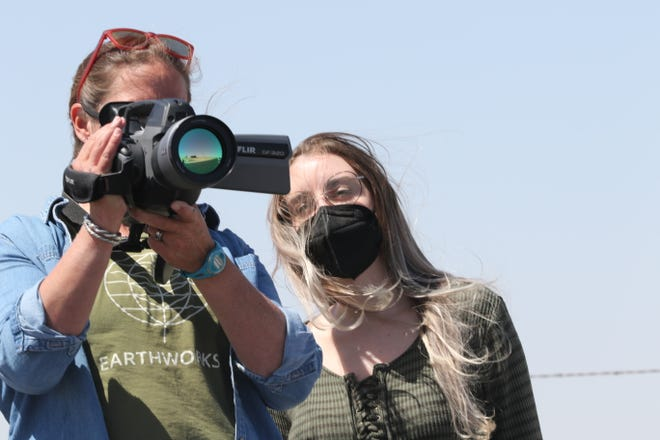Earthworks Field Organizer Nathalie Eddy (left) and Kayley Shoup with Citizens Caring for the Future observe potential emissions from oil and gas sites using a forward-looking infrared (FLIR) camera, April 7, 2021 in southern Eddy County.