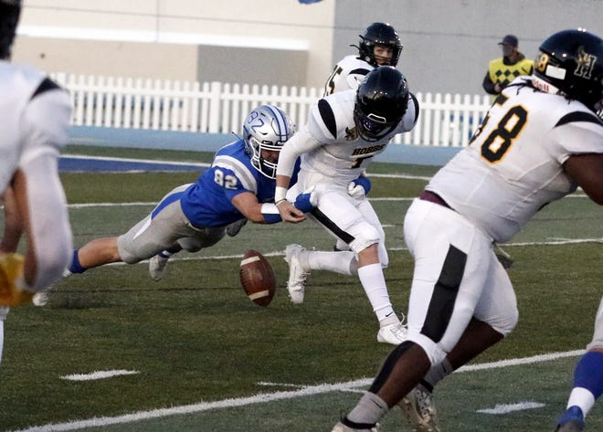 Carlsbad's Austin Blair strip sacks Hobbs' Colton Graham in the first quarter of their game on March 19, 2021. Carlsbad's defense forced six turnovers and won, 27-21.