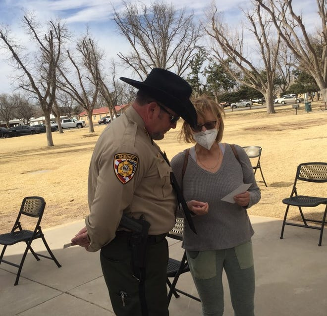 Eddy County Sheriff Mark Cage (left) and Eddy County DWI Program Director Cindy Sharif confer before a memorial service for slain New Mexico State Police officer Darian Jarrott in Carlsbad on Feb. 27, 2021.