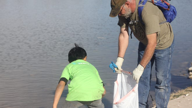 A.J. Prieto, 10, picks up trash along the Pecos River, March 10, 2018 at the Lower Tansil Dam.