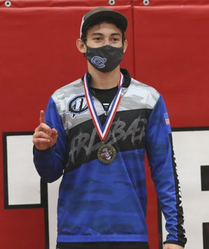 Logan Romero displays his District 3-5A wrestling medal in the 126-pound division on May 21, 2021. Romero will return to the state tournament for the second consecutive year.