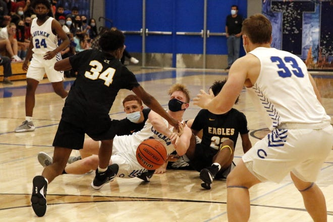 Carlsbad's Andrew Miller, center, passes to Ayden Parent (33) in the final minute of Friday's season finale against Hobbs. Parent made the basket and Carlsbad won, 49-47 to sweep the season series.