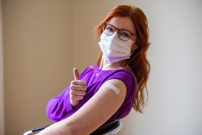 Woman wearing face mask looking at camera showing thumbs up after getting the covid-19 vaccine. Female gesturing thumbs-up sign after getting coronavirus vaccine at vaccination center.