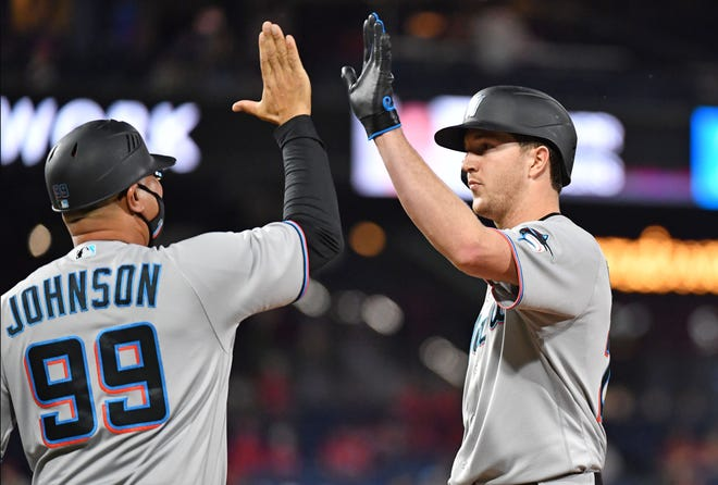 May 19, 2021; Philadelphia, Pennsylvania, USA; Miami Marlins starting pitcher Trevor Rogers (28) gets a high five from first base coach Kevin Johnson (99) after getting a base hit against the Philadelphia Phillies during the seventh inning at Citizens Bank Park. Mandatory Credit: Eric Hartline-USA TODAY Sports