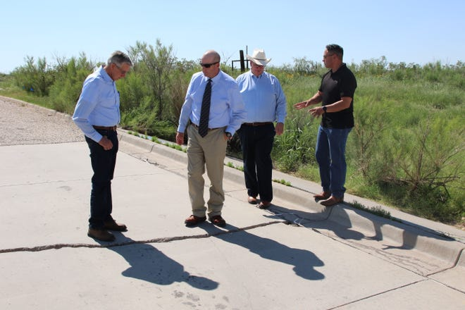 From left: Carlsbad Mayor Dale Janway, Scott Hicks of Smith Engineering, Deputy City Administrator KC Cass and Lt. Gov. Howie Morales look at flood damage along Hidalgo Road on July 9, 2021.