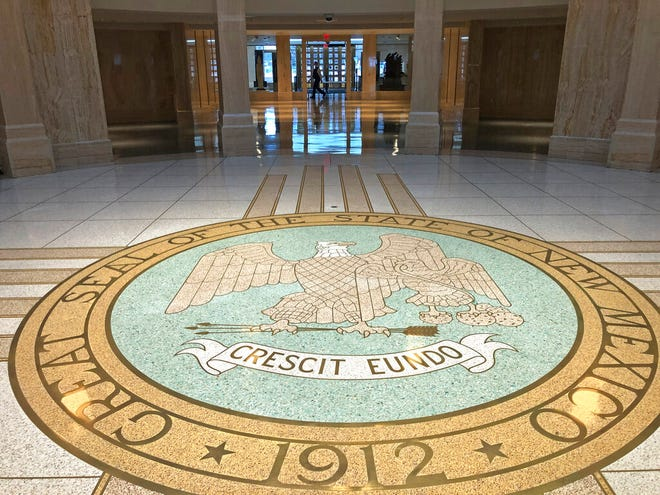 New Mexico state lawmakers trickle into the Statehouse on Tuesday, Jan. 19, 2021, in Santa Fe, N.M., on the first day of a 60-day legislative session.