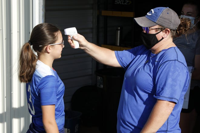 Cavegirls head soccer coach Misty Long checks the temperature of a soccer player before she's allowed to exercise on June 15, 2020. This was the first day student-athletes were allowed to exercise in limited groups due to COVID-19.