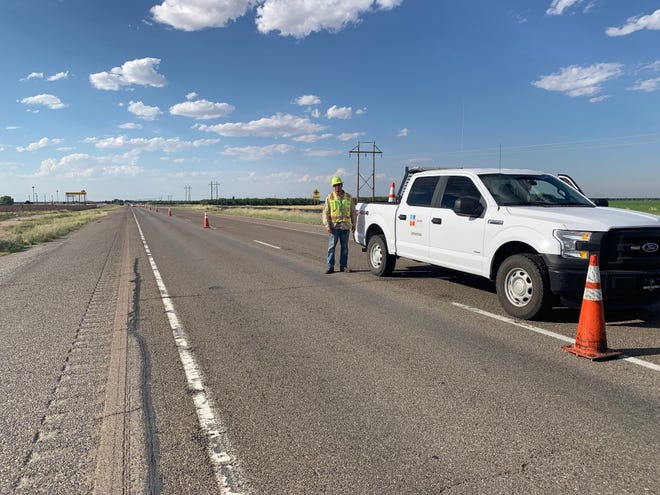 A New Mexico Department of Transportation places cones in preparation of a work project.