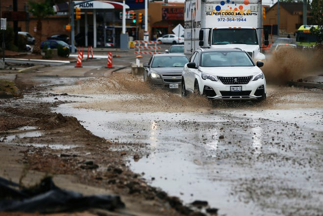 People drive through floodwaters on Mesa Street on Tuesday.