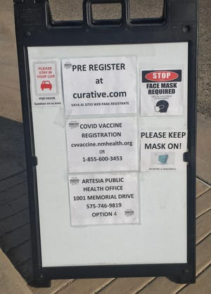 A sign at a drive thru COVID-19 clinic at the Eddy County Public Health Office in Artesia reminds people to register before getting tested or receiving a vaccine.