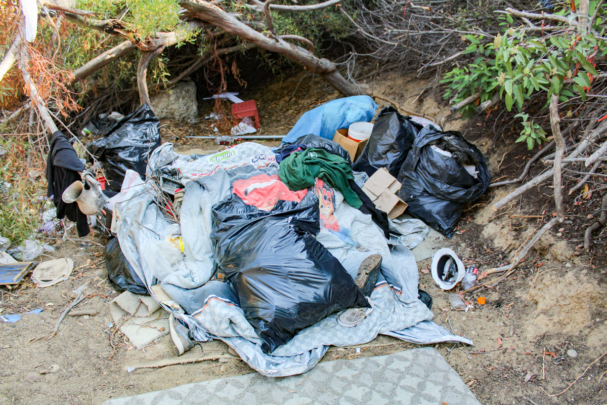 A heap of garbage, including bags of clothes, is just of hundreds of bags of garbage in an homeless camp adjacent to the freeway in Encinitas. Photo by Jordan P. Ingram