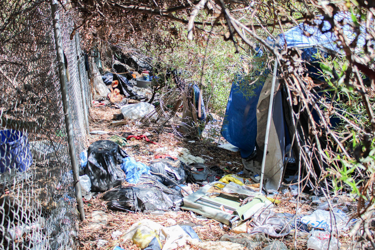 Several tents were found amidst piles of trash at a homeless encampment adjacent to the Interstate 5 northbound freeway offramp near Encinitas Boulevard. Photo by Jordan P. Ingram