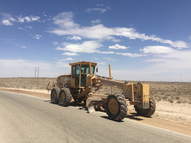 An Eddy County road grader performs dirt work on the side of Illinois Camp Road near Artesia on April 27, 2021.