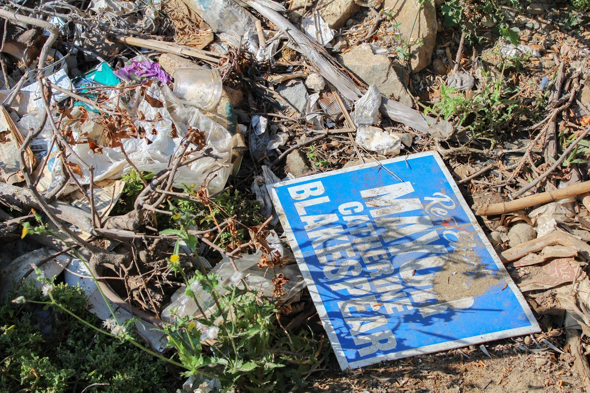 """A """"Re-Elect Catherine Blakespear"""" sign is found in a pile of garbage near a drainage tunnel connecting to Cottonwood Creek Park in Encinitas."""