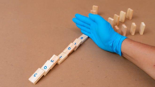 "Gloved hand between fallen wood dominoes spelling ""COVID-19"" and standing wood dominoes."